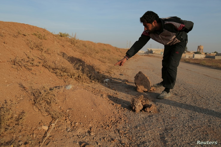A resident points to what he believes is a land mine in the village of al-Heesha in Raqqa district of Syria after it was captured from Islamic State, Nov. 15, 2016.