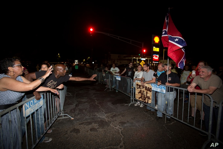Anti-monument protesters Rose Hunter, left, and her son, Deshaun Washington, make their case with pro-monument supporters, right, near the statue of Confederate Gen. P.G.T. Beauregard as the statue was prepared for removal from the entrance to City P...