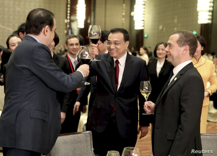 China's Premier Li Keqiang, center, toasts with Kazakhstan's Prime Minister Karim Massimov, left, and Russia's Prime Minister Dmitry Medvedev during a gala ahead of the 14th Shanghai Cooperation Organization Prime Ministers Meeting, in Zhengzhou, Hen...