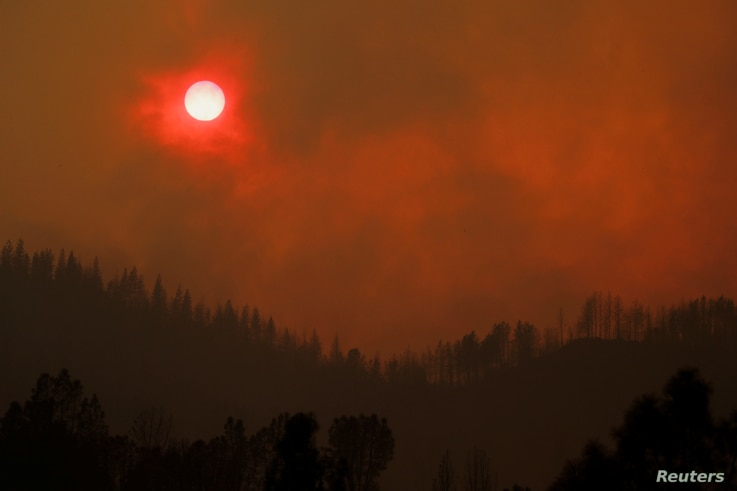 The setting sun is turned red by the smoke from the Carr Fire burning in the hills west of Redding, Calif., July 27, 2018.