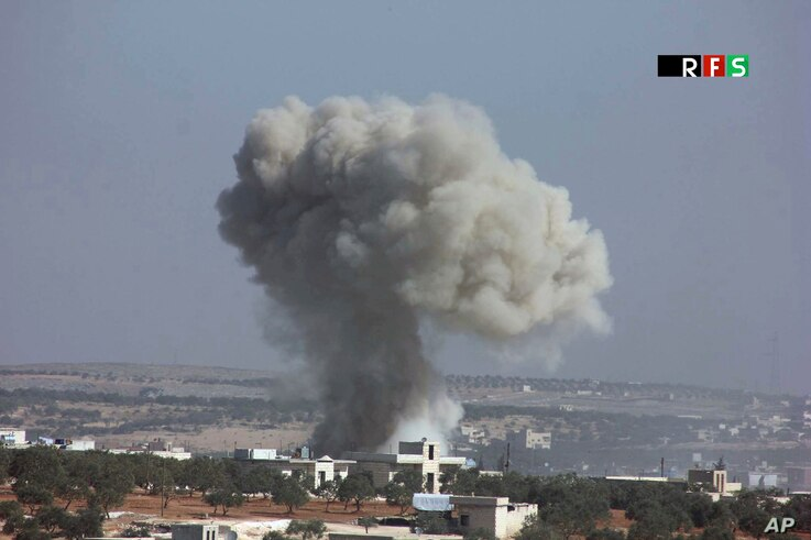 This photo provided by the Revolutionary Forces of Syria, an opposition activist media organization, which has been authenticated based on its contents and other AP reporting, shows an airstrike that killed over 20 people in the village of Hass, Syri...
