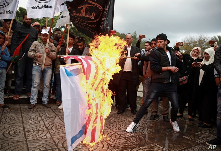 Palestinian demonstrators burn representations of Israeli and American flags during a protest against the possible U.S. decision to recognize Jerusalem as Israel's capital, in Gaza City, Dec. 6, 2017.