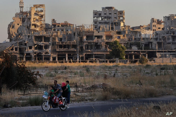 People ride their motorcycle by damaged buildings in the old town of Homs, Syria, Wednesday, Aug. 15, 2018.