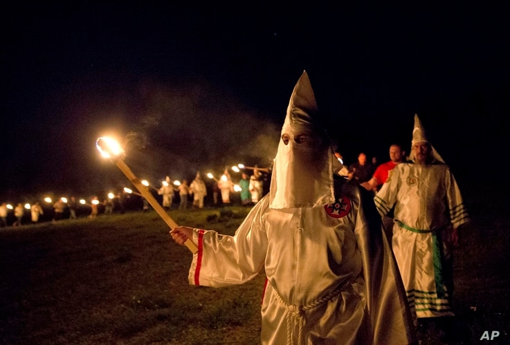 "In this Saturday, April 23, 2016 photo, members of the Ku Klux Klan participate in cross burnings after a ""white pride"" rally in rural Paulding County near Cedar Town, Ga. Born in the ashes of the smoldering South after the Civil War, the KKK died an..."