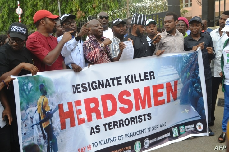 FILE - Demonstrators march and carry banner to protest bloody clashes between herdsmen and farmers in the vast central region that has claimed dozens of lives during a rally in Abuja, Nigeria, March 14, 2018.