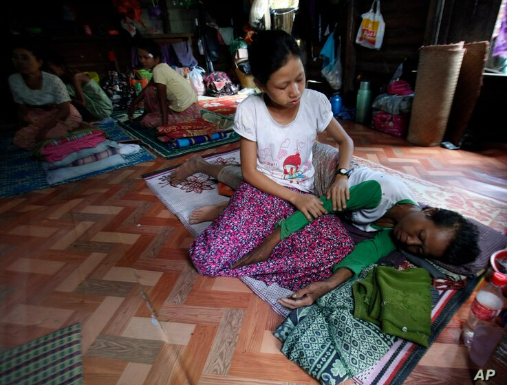 A daughter takes care of her HIV suffering mother as she rests in an HIV/AIDS shelter on the outskirts of Rangoon, Burma, Nov. 30, 2013.