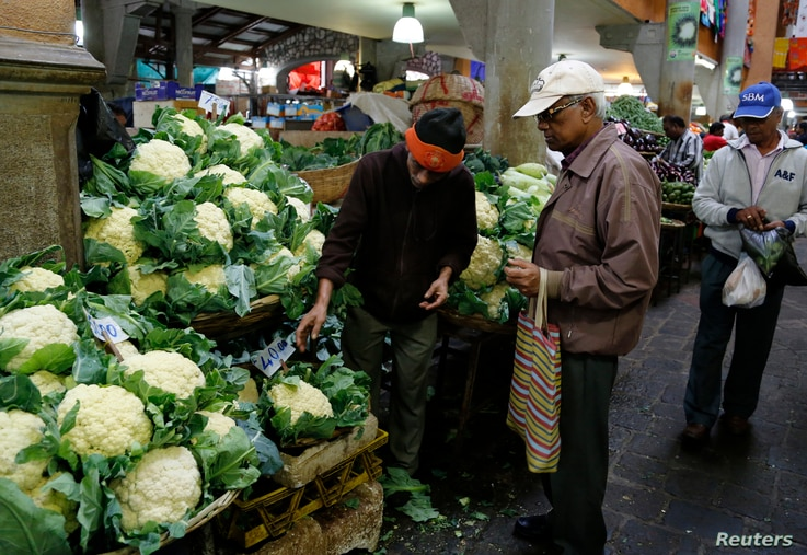 FILE - A vendor shows vegetables to customers at the market in Port Louis on the Indian Ocean island of Mauritius, Aug. 5, 2015.