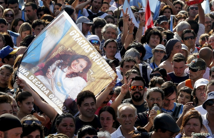 """People wait for the speech of Argentina's President Cristina Fernandez de Kirchner while carrying a banner that reads """"Gracias Cristina"""" during a rally in front of the Casa Rosada Presidential Palace in Buenos Aires, Argentina, Dec. 9, 2015."""