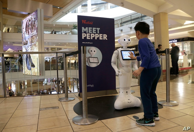 A boy gets to know Pepper the robot at the Westfield Mall in San Francisco, Dec. 22, 2016. Pepper has trouble understanding what people are asking, requiring shoppers to type in their requests for mall directions on a tablet mounted on the robot's ch...