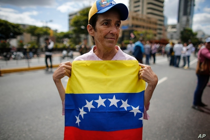 A woman holds a Venezuelan national flag as she takes part in a walk out against President Nicolas Maduro, in Caracas, Venezuela, Jan. 30, 2019.