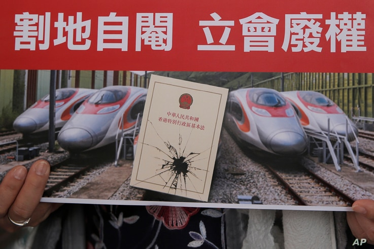 """FILE - An activist holds a card at a protest near the West Kowloon terminus of the Guangzhou-Shenzhen-Hong Kong Express Rail Link, Dec. 28, 2017. Some Hong Kong legal scholars say the """"co-location arrangement,"""" is unconstitutional, as it contravenes ..."""