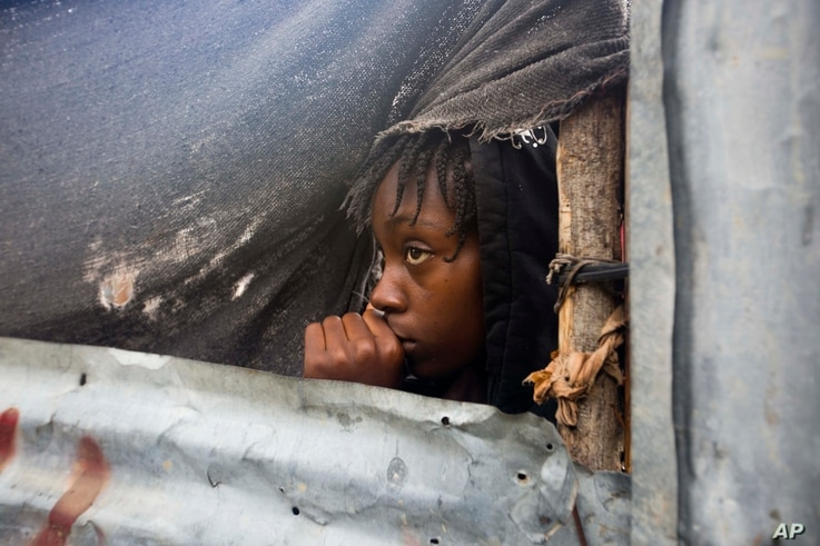 A girl watches as authorities arrive to evacuate people from her house in Tabarre, Haiti, Oct. 3, 2016.