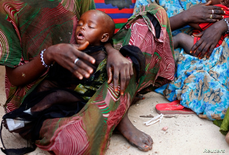 A woman holds her malnourished child in Sirlaabe IDP camp in Mogadishu, Somalia, June 28, 2012.