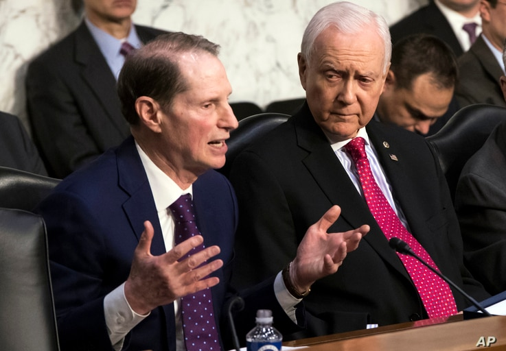 Sen. Ron Wyden, D-Ore., left, the top Democrat on the Senate Finance Committee, criticizes the Republican tax reform plan while Chairman Orrin Hatch, R-Utah, listens to his opening statement as the panel begins work overhauling the nation's tax code,...