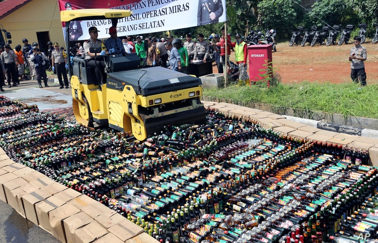 Police use a road roller to destroy bottles of illegal alcohol confiscated in Serpong, on the outskirts of Jakarta, Indonesia, April 13, 2018. Deaths from drinking toxic bootleg alcohol in Indonesia have exceeded 100 this month, police said as they v...