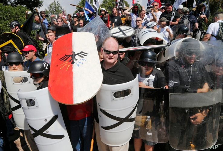 White nationalist demonstrators use shields as they guard the entrance to Lee Park in Charlottesville, Va., Aug. 12, 2017.