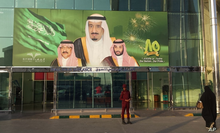 FILE - Images of King Salman, center, Crown Prince Mohammed bin Nayef, left, and Deputy Crown Prince Mohammed bin Salman hang at the entrance of a shopping center in Riyadh, Saudi Arabia, Dec. 14, 2015.