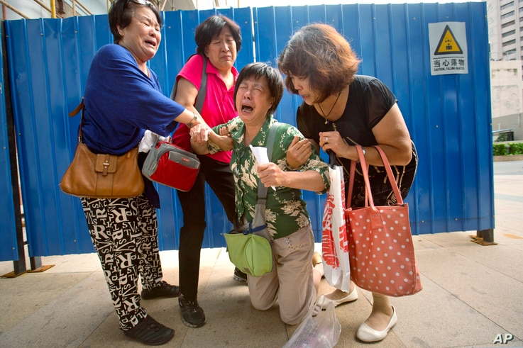 Bao Lanfang, second from right, whose daughter-in-law, son and granddaughter were aboard Malaysia Airlines Flight 370, kneels in grief while speaking to journalists outside the company's offices in Beijing, Aug. 6, 2015.