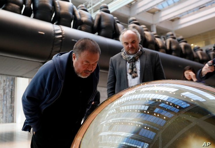 Chinese activist and artist Ai Weiwei looks into a glass ball which is part of his installation at the National Gallery in Prague, Czech Republic, March 16, 2017.