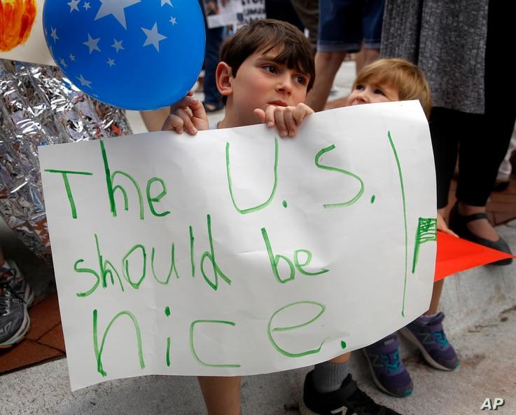 Shua Rich, age 6, holds his sign as he protests with his mother during a rally against U.S. immigration policies outside an office for Rep. Kevin Yoder, June 22, 2018, in Overland Park, Kan.