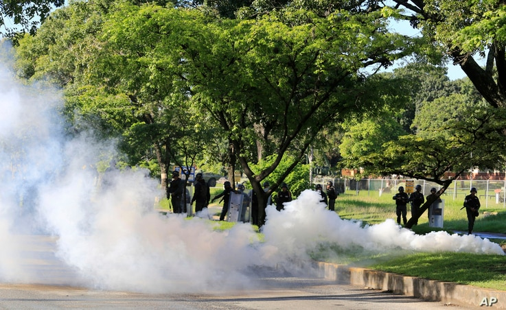 Venezuelan Bolivarian National Guard officers fire tear gas toward residents that try to walk to the Paramacay military base in Valencia, Venezuela, Aug. 6, 2017.