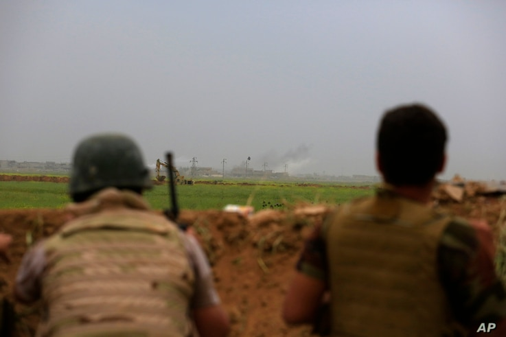 Smoke rises from positions in the Islamic State group held town of Besher, during a military operation to regain control of the small town, outside the oil-rich city of Kirkuk, 180 miles (290 kilometers) north of Baghdad, Iraq, April 10, 2016.