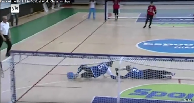 Screen grab from the YLE broadcast of the women's gold medal match at the 2014 IBSA Goalball World Championships in Espoo, Finland. The first throw by Asya Miller (in red) scored a goal that led to victory over Russia.