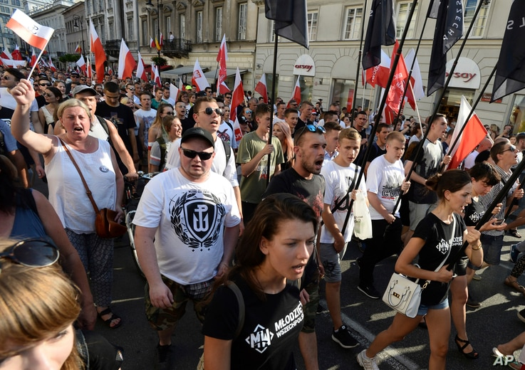 Far right wing activists shout slogans as they march through the downtown to commemorate the 73rd anniversary of the 1944 Warsaw Uprising in Warsaw, Poland, Aug. 1, 2017.