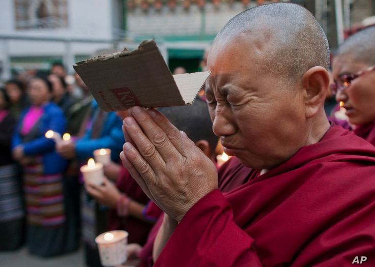 An exile Tibetan nun cries as she prays during a candlelit vigil in solidarity with two Tibetans, who exiles claim have immolated themselves demanding freedom for Tibet, in Dharmsala, India, Wednesday, March 2, 2016.