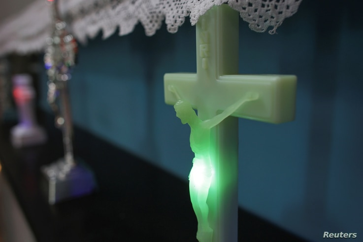 A LED light shines inside a plastic rendition of Jesus Christ on the cross at the newly opened kitsch museum in Bucharest, Romania, May 5, 2017.