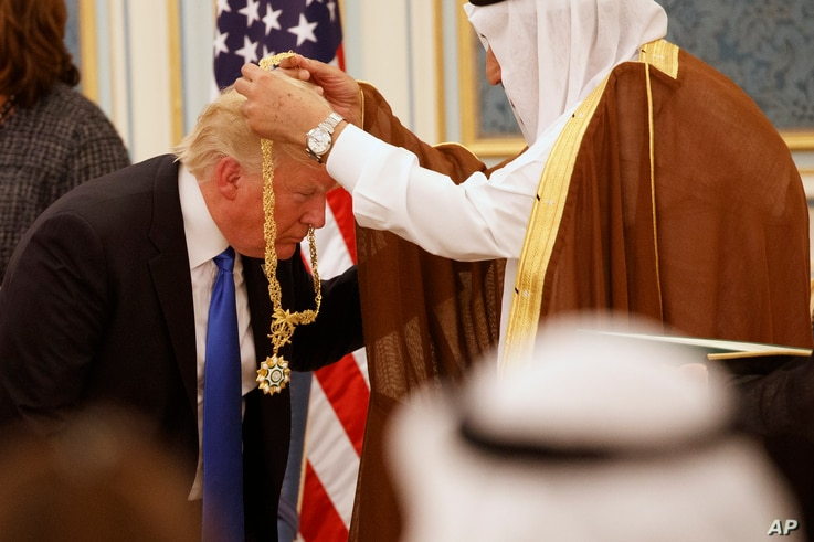 Saudi King Salman presents President Donald Trump with The Collar of Abdulaziz Al Saud Medal at the Royal Court Palace, Saturday, May 20, 2017, in Riyadh.