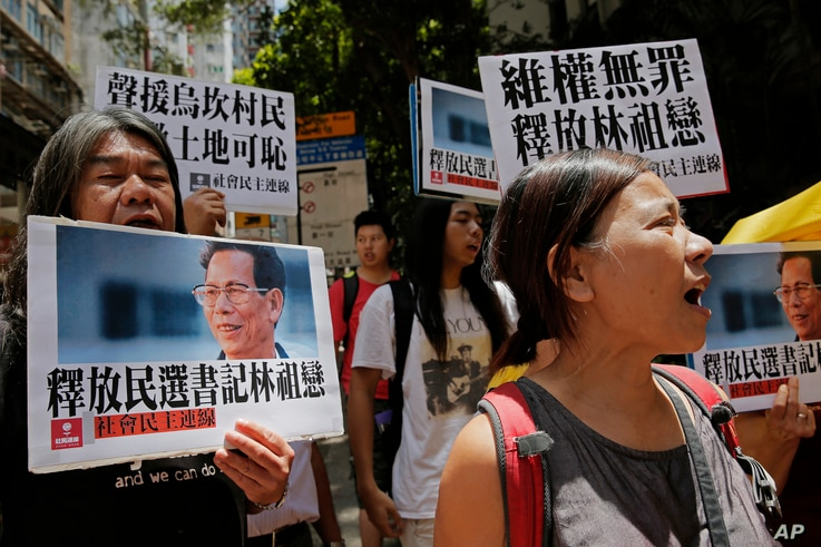 Protesters hold pictures of the Wukan village's 70-year-old leader, Lin Zuluan during a protest in Hong Kong, June 21, 2016.