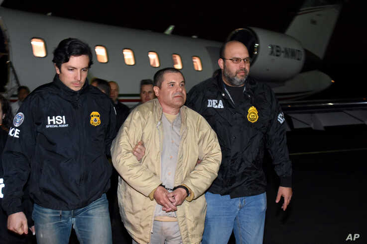 In this photo provided U.S. law enforcement, authorities escort Joaquin 'El Chapo' Guzman, center, from a plane to a waiting caravan of SUVs at Long Island MacArthur Airport, Jan. 19, 2017, in Ronkonkoma, N.Y.