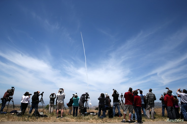 People watch as the Ground-based Midcourse Defense (GMD) element of the U.S. ballistic missile defense system launches during a flight test from Vandenberg Air Force Base, Calif., May 30, 2017.