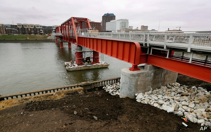 In this March 28, 2017, photo, the Red Bridge pedestrian bridge is seen over the Des Moines River in Des Moines, Iowa. A little more than a decade after it was restored, crews went back to the site with a crane to hoist the span more than 4 feet high...