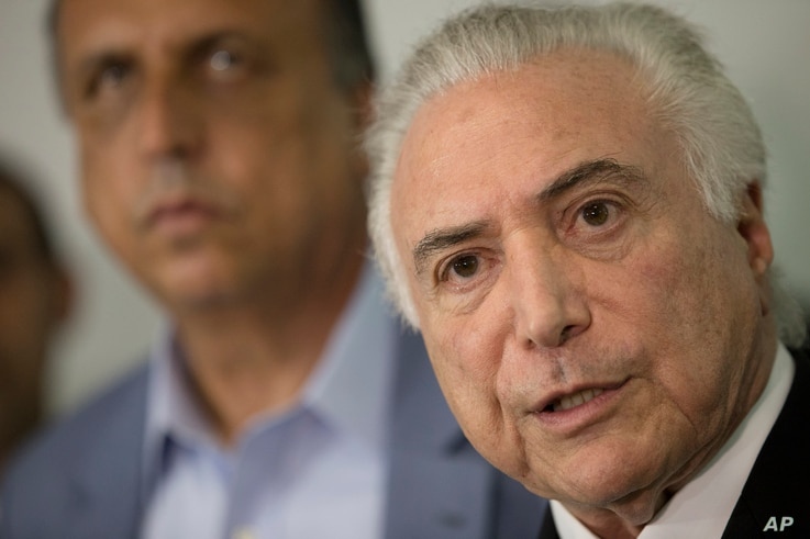 Brazil's President Michel Temer, right, talks to the press next to the Governor of Rio de Janeiro Luiz Fernando Pezao after a meeting with local authorities about the implementation of a decree that has placed the military in charge of Rio's state se...