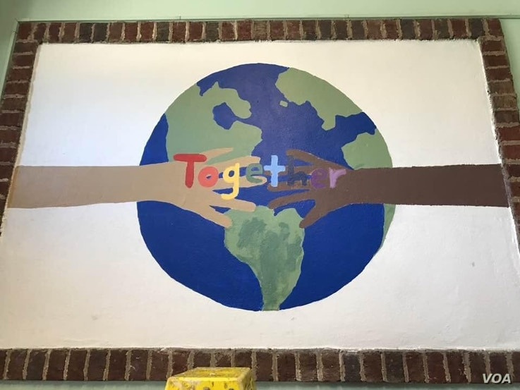 """Peacekeepers"" at a Montessori school made this mural after a workshop with ""Serve to Unite"" - the organization started by the son of one of the victims of the 2012 shooting."