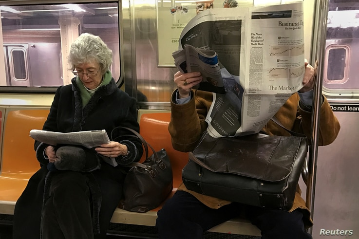 People ride the subway as they read newspapers as the train pulls into the Times Square in Manhattan, New York, Feb. 17, 2017.