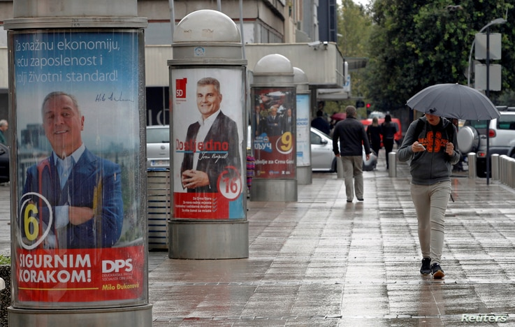 A man walks past election posters ahead of the parliamentary elections in Podgorica, Montenegro, Oct. 6, 2016.