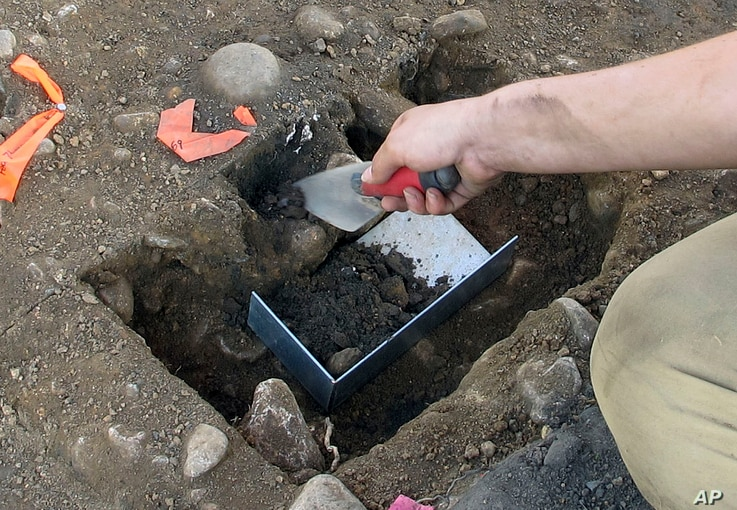 Emma Wink, part of an archaeological team, digs at the site of a 1600's Native American fort in Norwalk, Conn., Aug. 28, 2018.