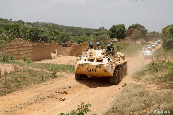 United Nations peacekeeping force vehicles drive by houses destroyed by violence in September, in the abandoned village of Yade, Central African Republic, April 27, 2017.