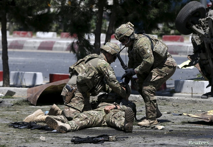 U.S. soldiers attend to a wounded soldier at the site of a blast in Kabul, Afghanistan June 30, 2015. At least 17 people were wounded in a suicide bomb attack on NATO troops as their truck convoy passed down the main road running between Kabul's airp...