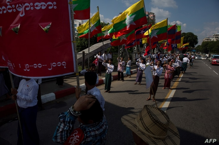 Men carry Myanmar national flags as they march in a show of support for the country's military and civil servants, in Yangon, Myanmar, Oct. 29, 2017.