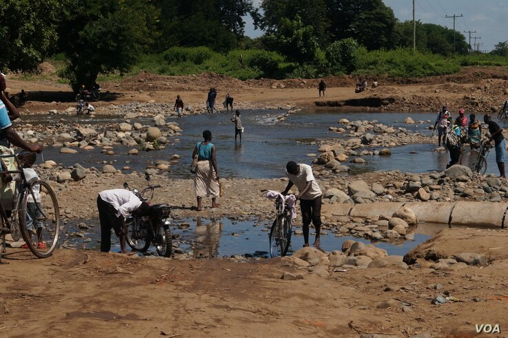 Residents of the heaviest-hit southern areas of Malawi struggle to cross the road, which is largely cut off by flooding brought by Cyclone Idai.