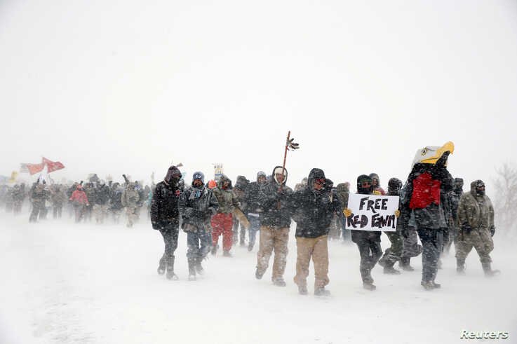 """Veterans join activists in a march just outside the Oceti Sakowin camp during a snow fall as """"water protectors"""" continue to demonstrate against plans to pass the Dakota Access pipeline adjacent to the Standing Rock Indian Reservation, near Cannon Bal..."""