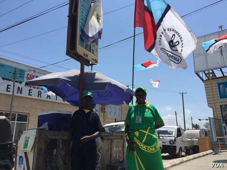 Tanzanians wearing ruling party CCM promotional clothing stand underneath opposition party Chadema flag in Dar es Salaam, Oct. 23, 2015.  (Photo: Jill Craig / VOA)