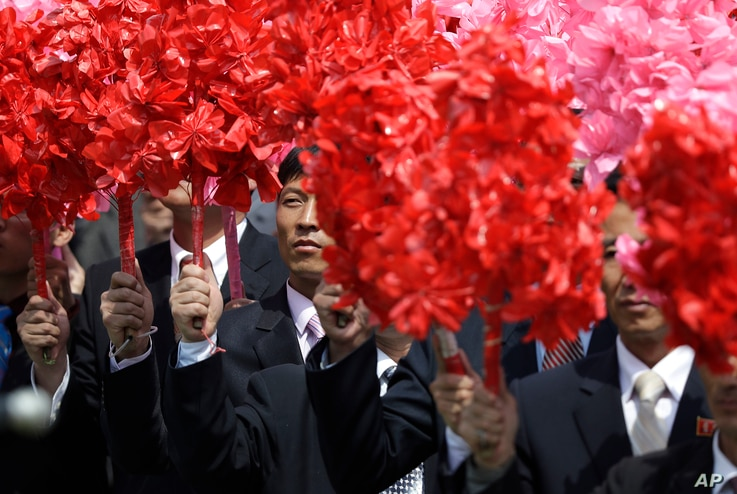 North Koreans wave plastic flowers during a military parade in Pyongyang to celebrate the 105th birth anniversary of Kim Il Sung, the country's late founder and grandfather of current ruler, Kim Jong Un, April 15, 2017.
