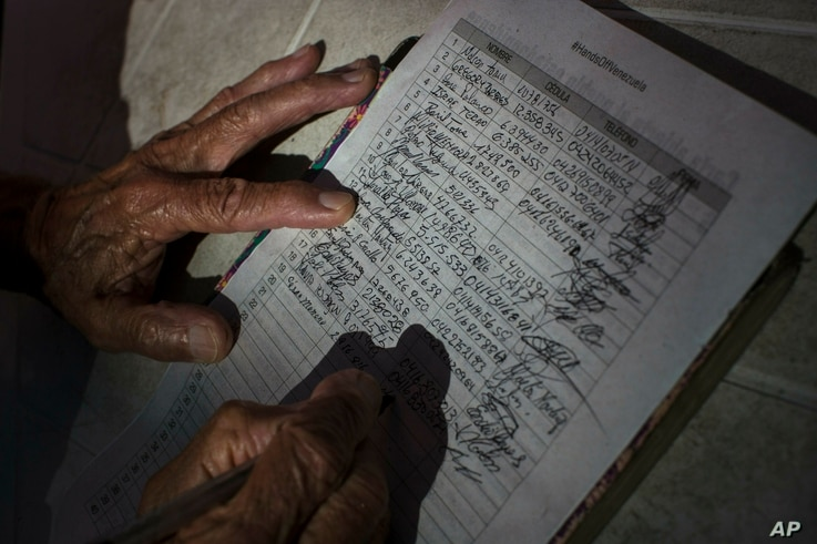 A man signs a petition during a campaign to collect signatures against the interference of the United States in the internal politics of Venezuela in Caracas, Venezuela, Feb. 9, 2019.