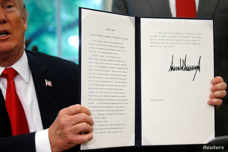 U.S. President Donald Trump displays an executive order on immigration policy after signing it in the Oval Office at the White House in Washington, June 20, 2018.