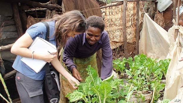 One of Nairobi's urban farmers shows international agricultural researcher Danielle Nierenberg some of the crops she's growing near her shack in Kibera slum
